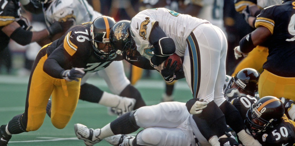 PITTSBURGH, PA - NOVEMBER 22: Defensive lineman Kevin Henry #76 and linebacker Earl Holmes #50 of the Pittsburgh Steelers tackle running back Fred Taylor #28 of the Jacksonville Jaguars during a game at Three Rivers Stadium on November 22, 1998 in Pittsburgh, Pennsylvania. The Steelers defeated the Jaguars 20-15. (Photo by George Gojkovich/Getty Images)