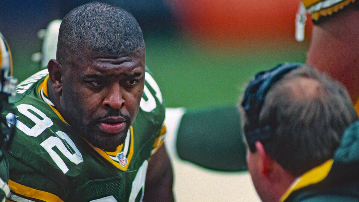 Green Bay Packers player Reggie White talking to head coach, Mike Holmgren.