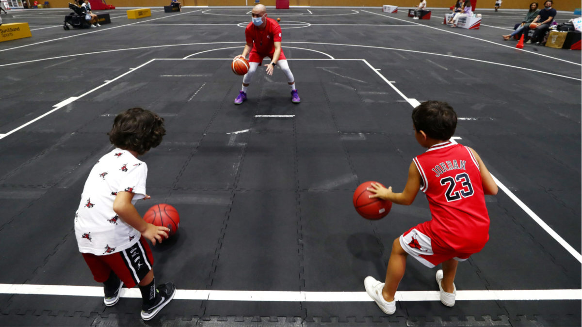 DUBAI, UNITED ARAB EMIRATES - JULY 08: A basketball coach show kids how to dribble a ball at Dubai Sports World on July 08, 2020 in Dubai, United Arab Emirates. Dubai Sports World is the UAE's largest indoor summer sports venue. (Photo by Francois Nel/Getty Images)