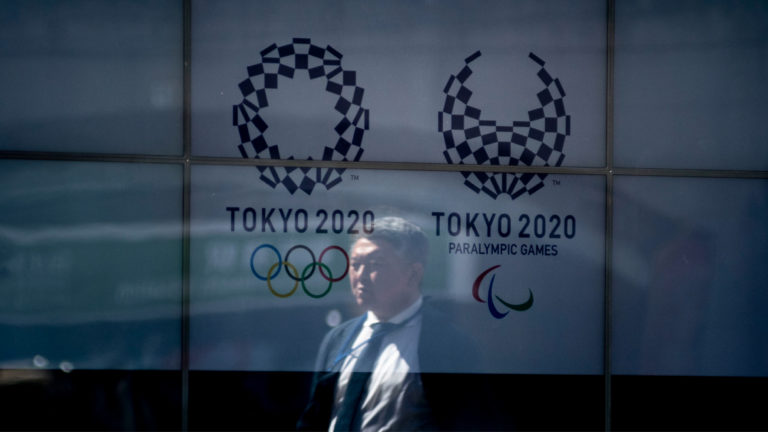 People walk past a screen showing logo the Tokyo 2020 Olympic Games and Tokyo 2020 Paralympic Games after the announcement of the games postponement to the summer of 2021. Japan, March 24, 2020. (Photo by Alessandro Di Ciommo/NurPhoto via Getty Images)