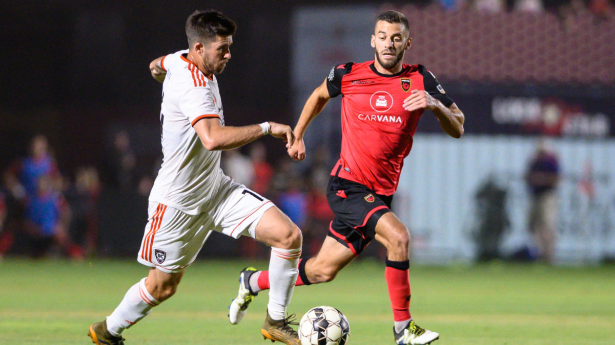 PHOENIX, ARIZONA - JUNE 15: Aodhan Quinn #14 of Orange County SC is challenged for the ball by Joey Calistri #21 of Phoenix Rising FC during the USL match between Orange County FC and Phoenix Rising FC at Casino Arizona Field on June 15, 2019 in Phoenix, Arizona. (Photo by Joe Hicks/Getty Images)