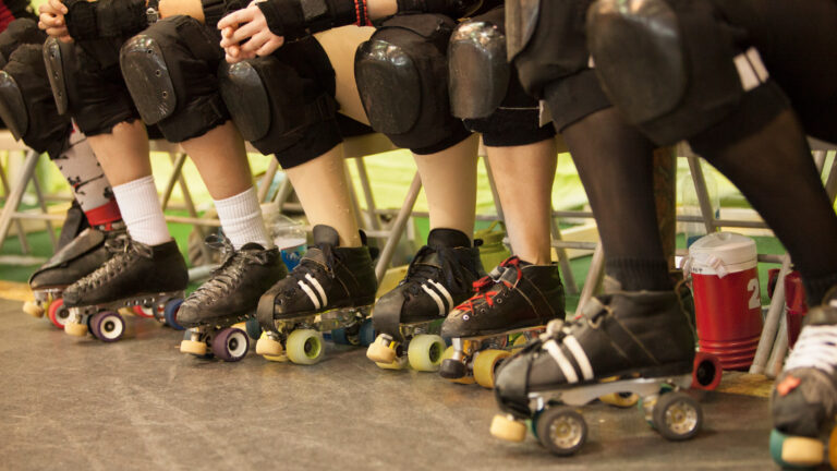 Photo of roller derby players knees, knee pads and in roller skates, seated in a row.