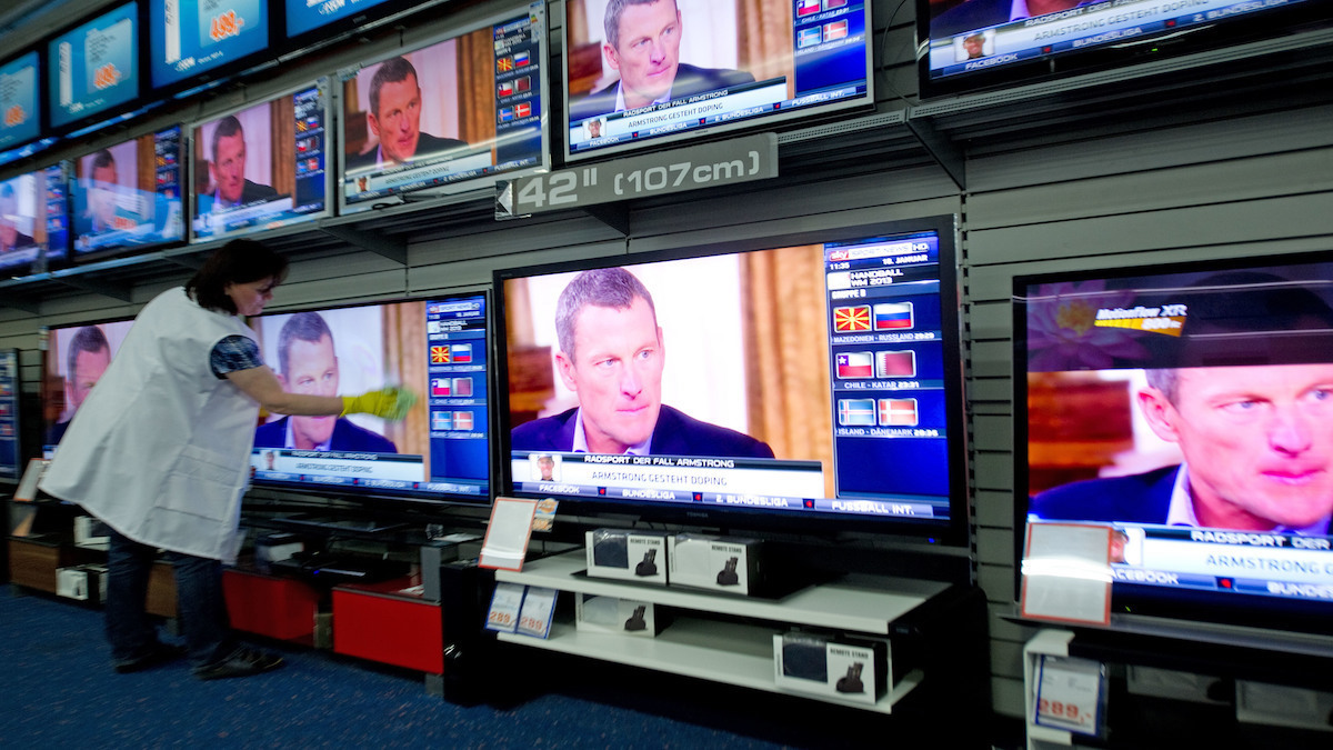 A store employee cleans TV screens displaying US cyclist Lance Armstrong