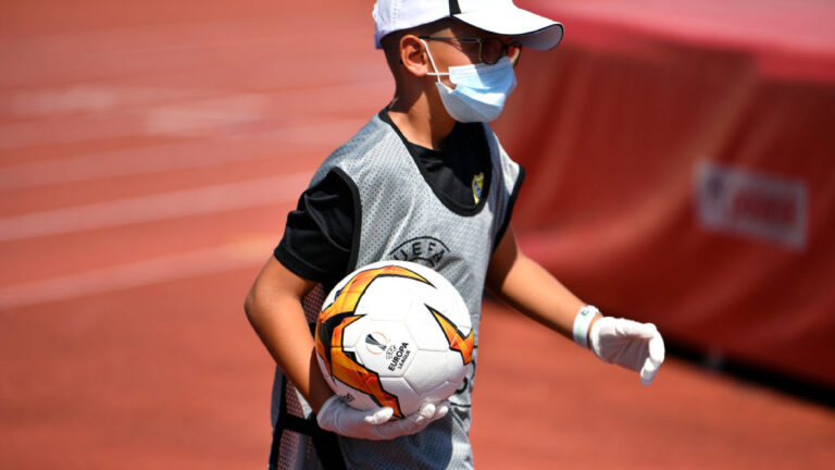 NYON, SWITZERLAND - AUGUST 08: S.S. A ball boy wearing protective equipment on during the UEFA Champions League 2020/21 Preliminary Round Semi-final match between S.S. Tre Fiori F.C. and Linfield FC at Colovray Sports Center on August 8, 2020, in Nyon, Switzerland (Photo by Harold Cunningham - UEFA/UEFA via Getty Images)