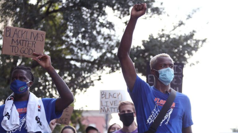 Althletes from the University of Florida march with Black Lives Matter signs