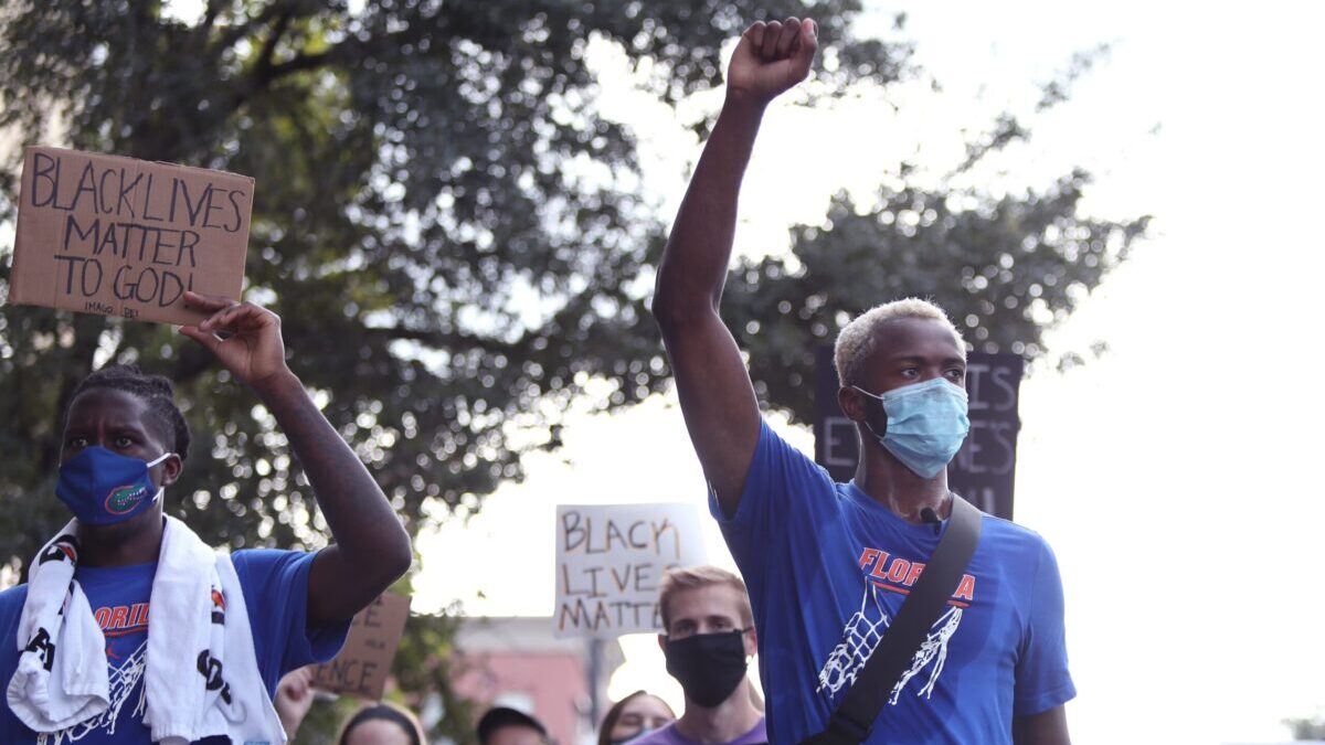 University of Florida athletes Scottie Lewis and Anthony Duruji march with Black Lives Matter signs.