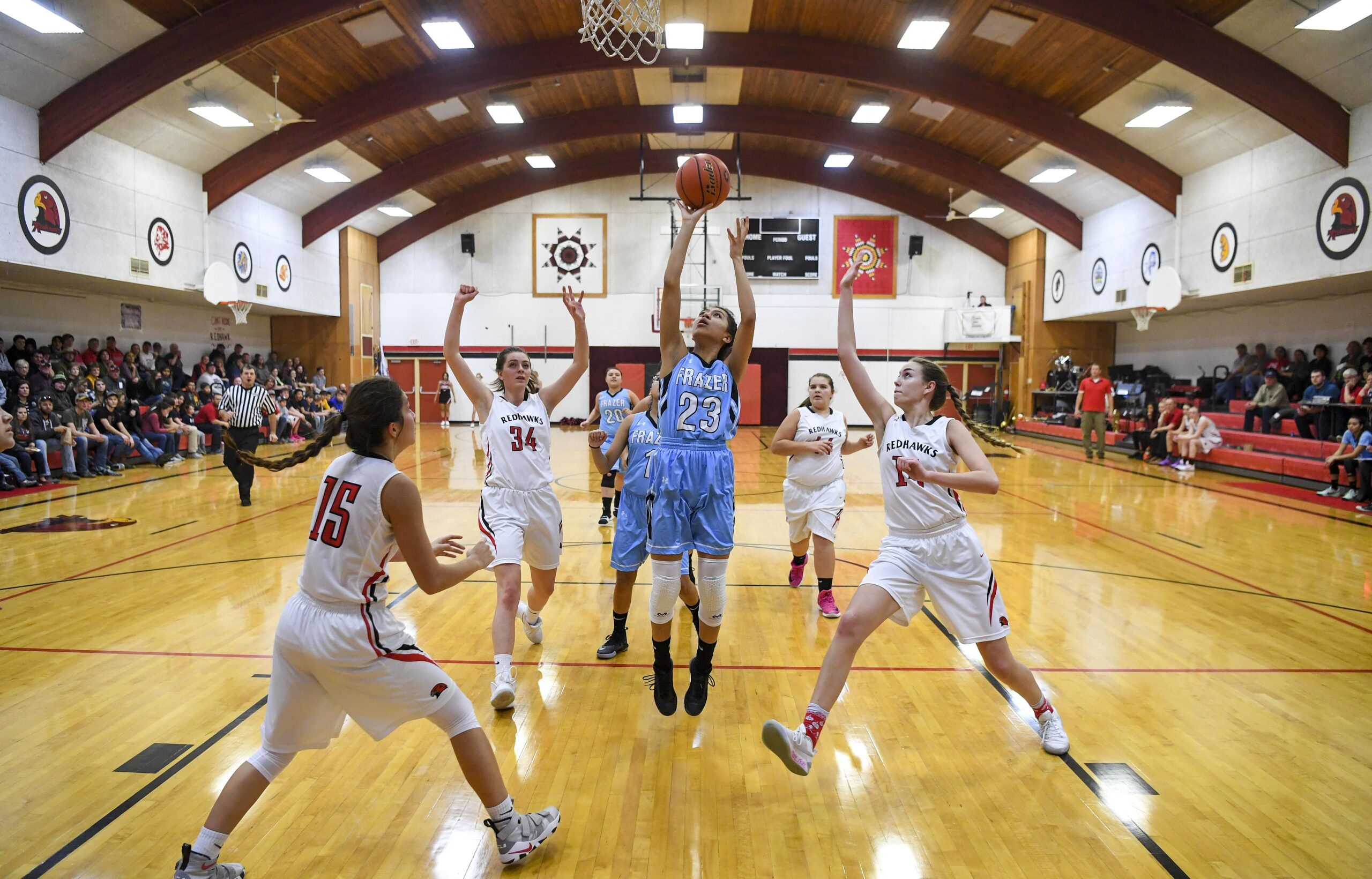 Native American girl's basketball team playing in a basketball game