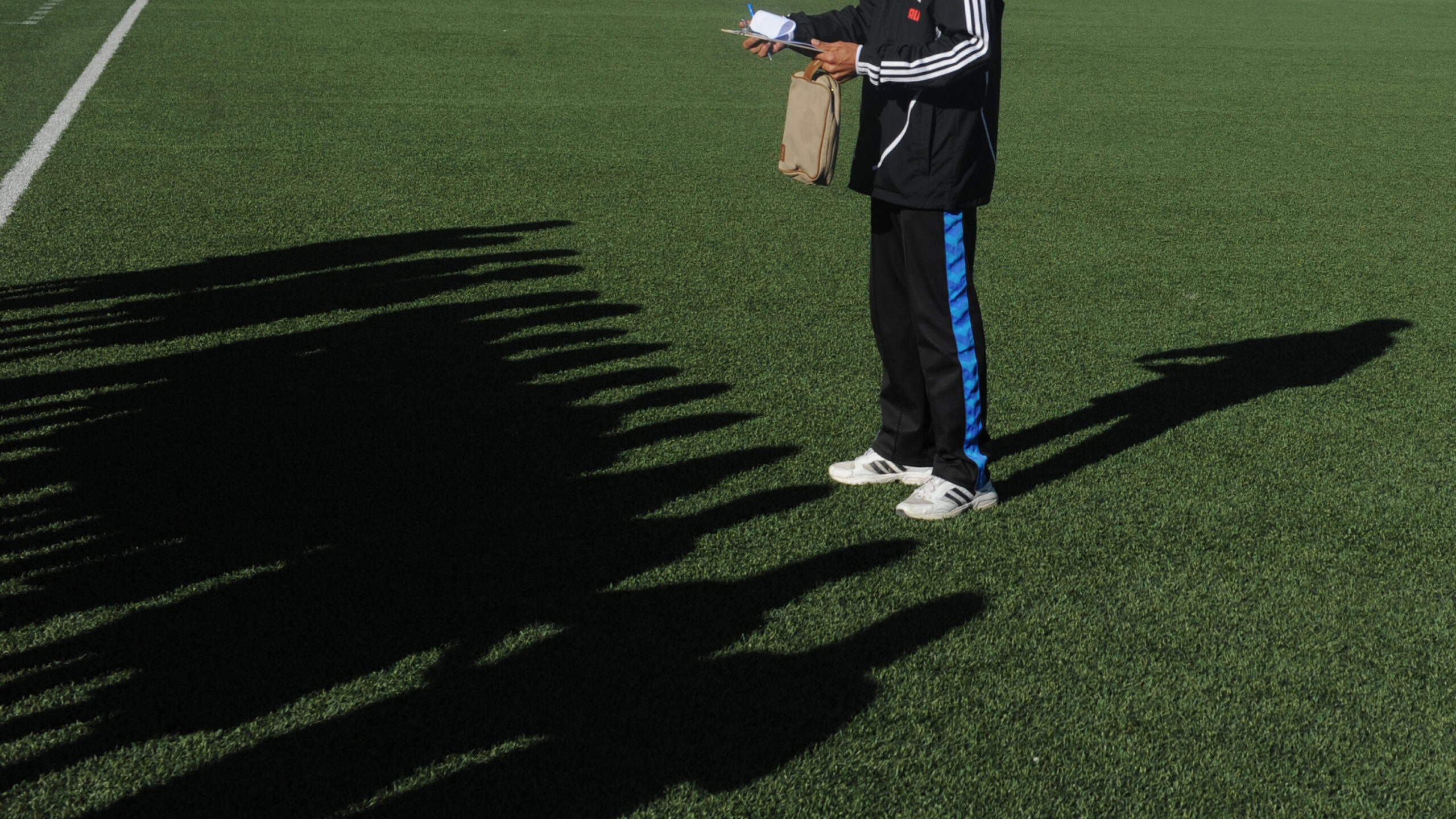 Shadows of Afghan female football players fall as their coach gives instructions prior to a football match in Kabul on November 9, 2013. Twelve teams played in Kabul with players to be selected for the Afghanistan National Women Football Team. AFP PHOTO/ Farshad USYAN (Photo credit should read FARSHAD USYAN/AFP via Getty Images)