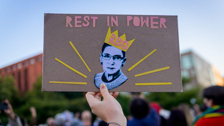 "A Ruth Bader Ginsburg poster saying ""Rest in Power RBG"" being held by a hand."