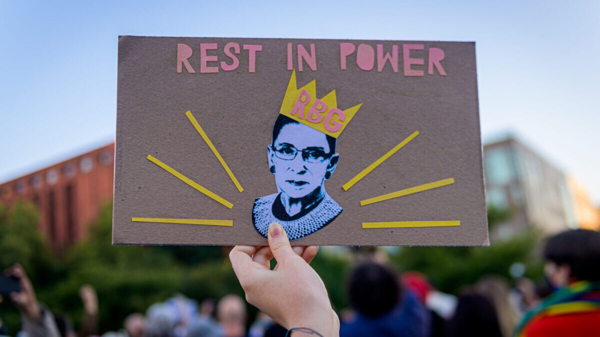 """A Ruth Bader Ginsburg poster saying """"Rest in Power RBG"""" being held by a hand."""