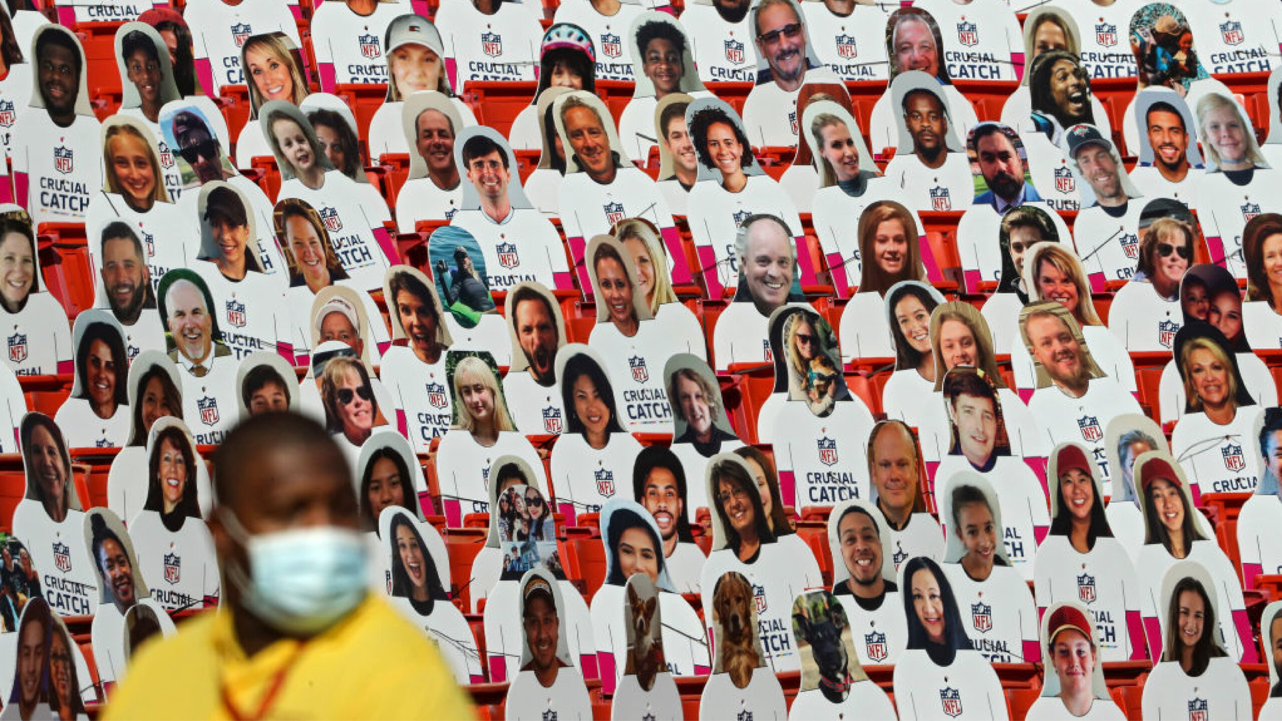 LANDOVER, MARYLAND - OCTOBER 04: Cardboard cutouts of fans are seen in the spectator seating in front of a security guard wearing a surgical face mask during the second half at FedExField on October 4, 2020 in Landover, Maryland. Due to the coronavirus pandemic, the Washington Football Team did not host fans during the game. (Photo by Patrick Smith/Getty Images)