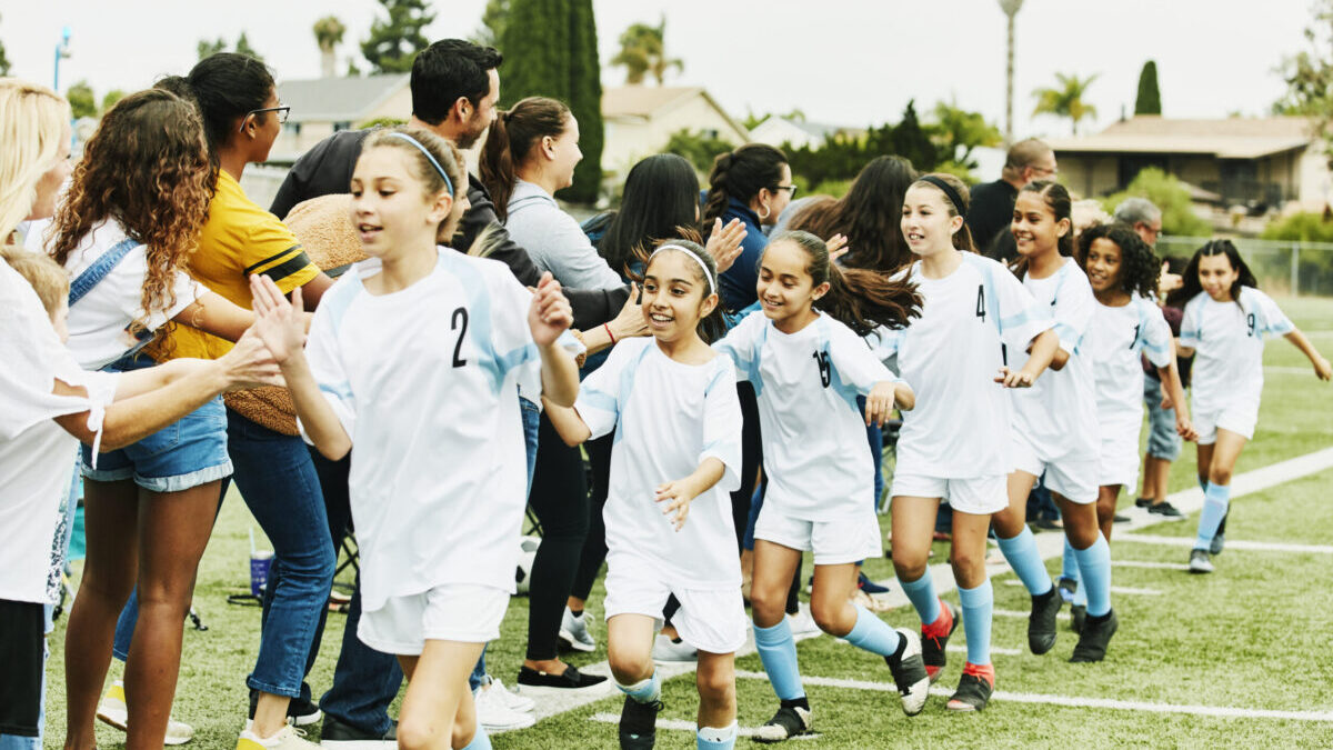 Youth girls soccer team high-fiving fans