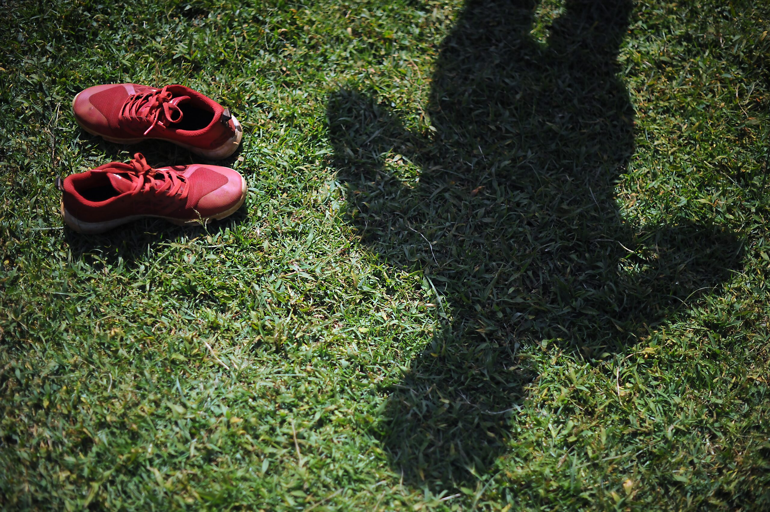 An athlete's shadow faces grass with a pair of red sneakers on the side