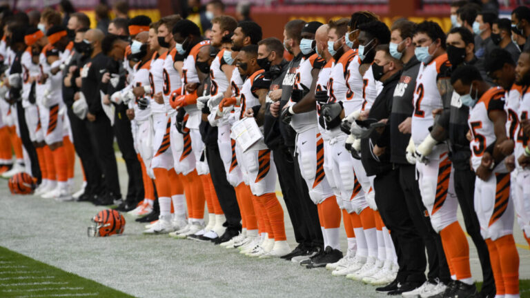 Cincinatti Bengals team lock arms on the sidelines of football field while wearing masks