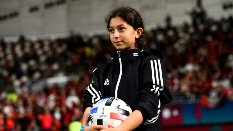 A young girl watches a soccer game with a ball in hand