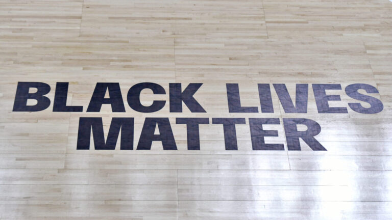 A Black Lives Matter logo on a basketball court floor