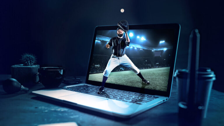 A baseball player catching the ball superimposed on a laptop