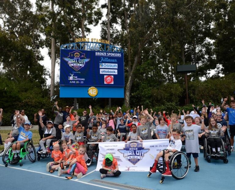 A large group photo of youth adaptive athletes on a court; many of them are waving their hands in the air. (Photo courtesy of Angel City Sports)