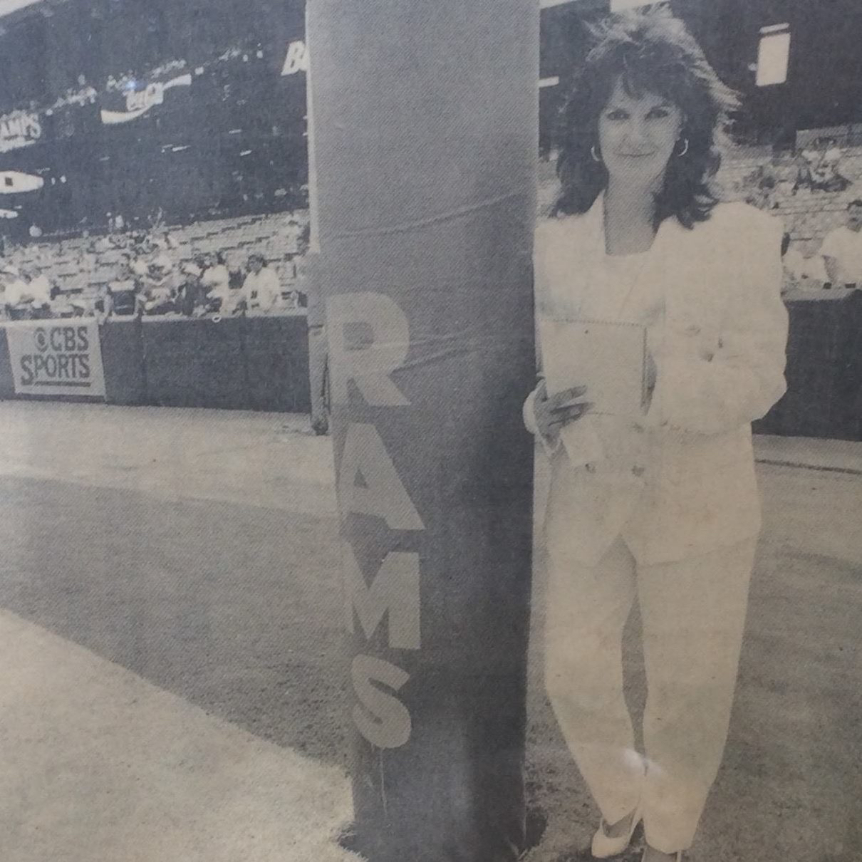 A black and white photo of Paola Boivin in front of the LA Rams goal post.