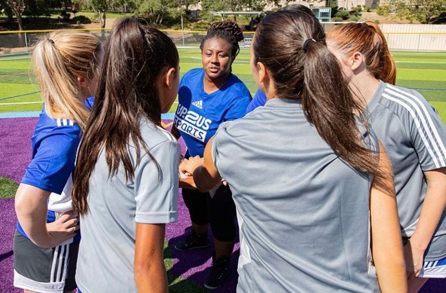 A group of female athletes on a field, with their hands in a huddle. (Photo courtesy of Up2Us Sports)