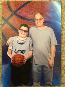 The author and his son pose during a youth sports basketball season.