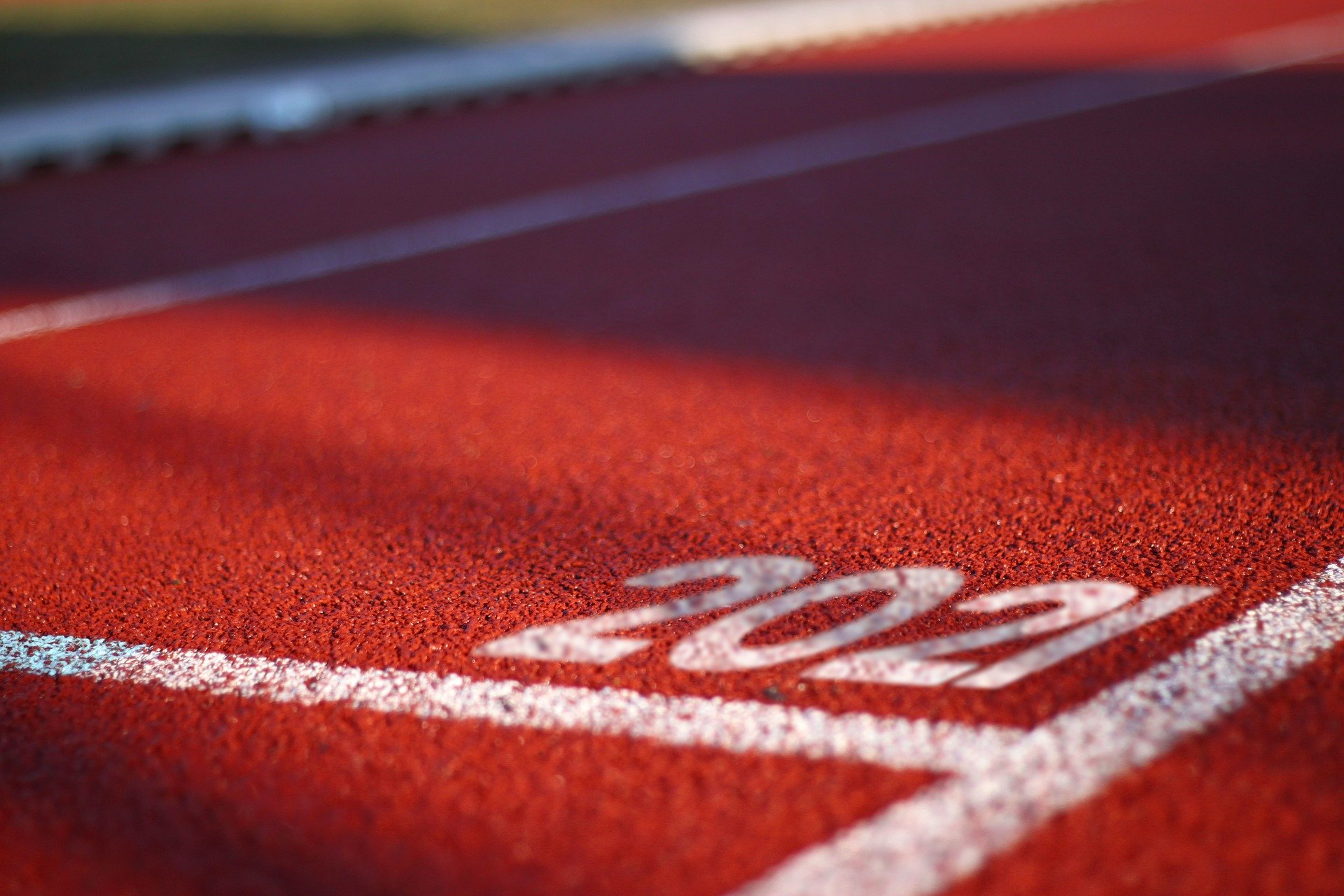 Close up of the lines on a running track, the typical lane numbers are replaced by '2021' (Photo via Pixabay)
