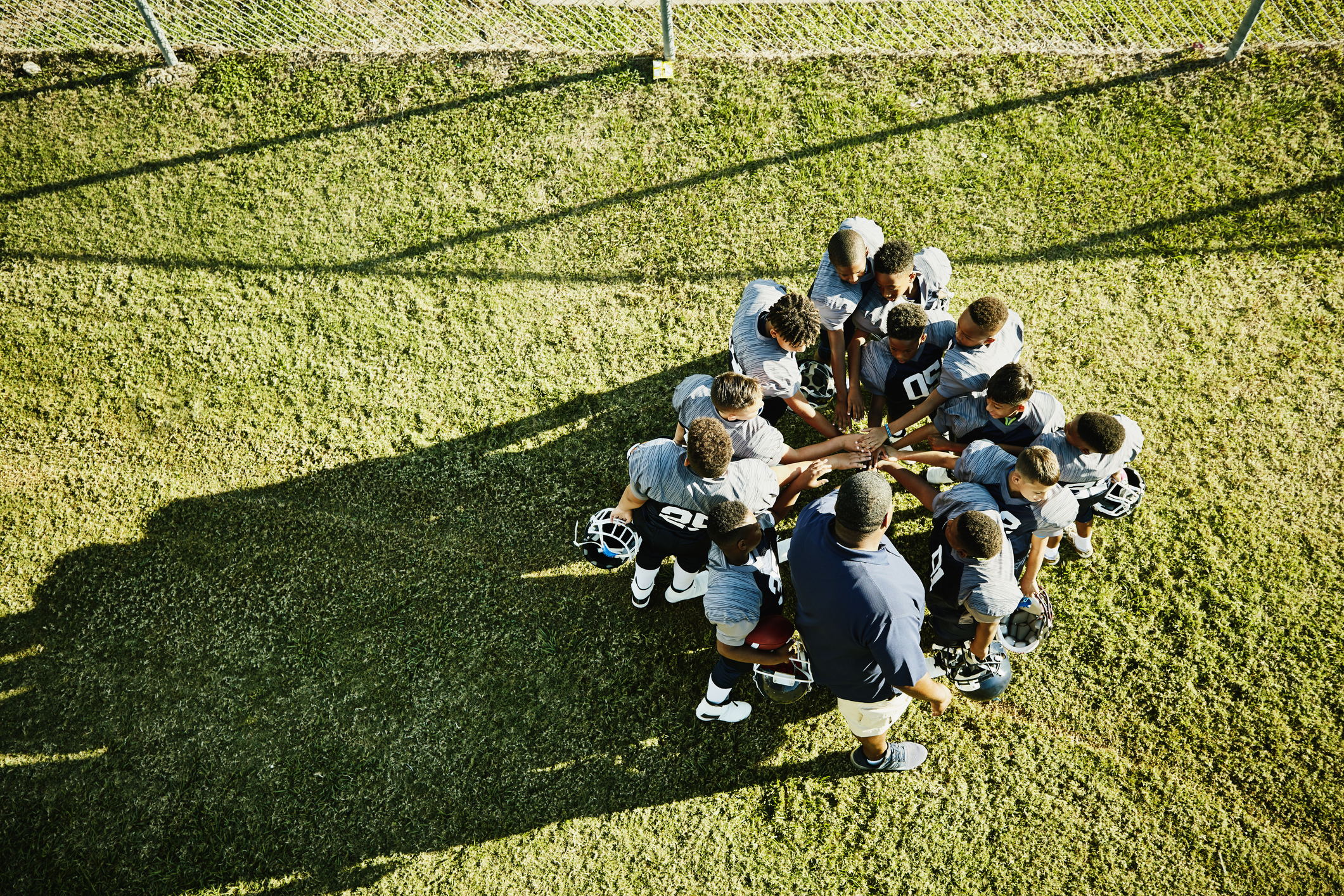 Overhead view of coach and football team gathered in circle with hand together before football game