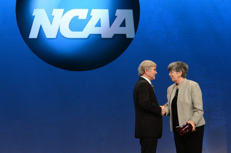 Donna Lopiano embraces Mark Emmert at an NCAA event.