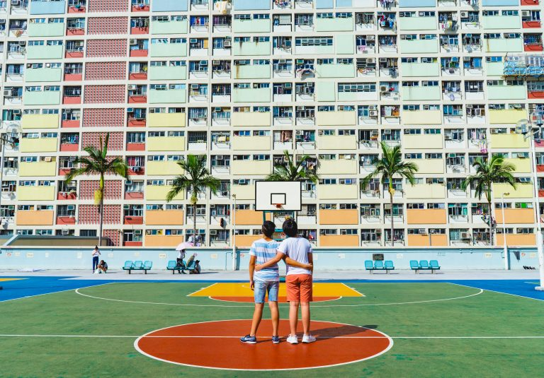 Two young children stand arm in arm on a colorful basketball court with a colorful housing building in the background